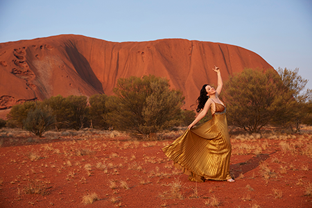 A woman stands in front of Uluru in a gold dress