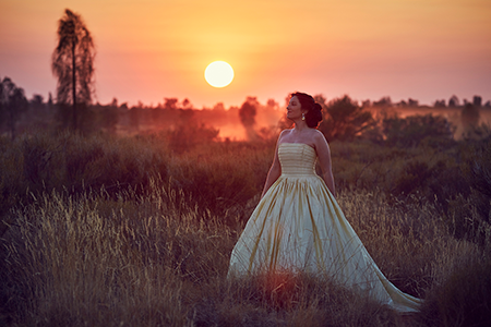 A woman in a yellow dress stands in a field in front of a sunset