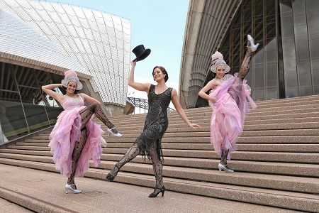 Singer Julie Lea Goodwin stands on the steps of the Sydney Opera House in a black gown with two dancers in pink either side