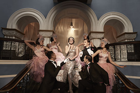 Singer Julie Lea Goodwin stands on a large staircase wearing a gold dress, surrounded by dancers in formal wear