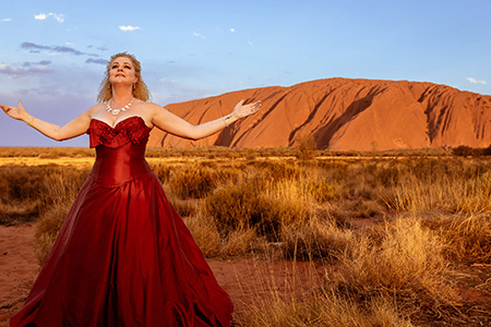 A woman in a red dress stands in front of Uluru with her arms spread