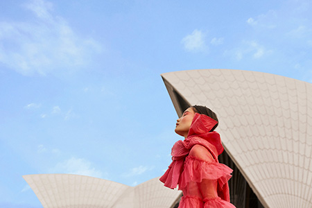 A woman in a red dress stands in front of the white sails of the Sydney Opera House and a bright blue sky.