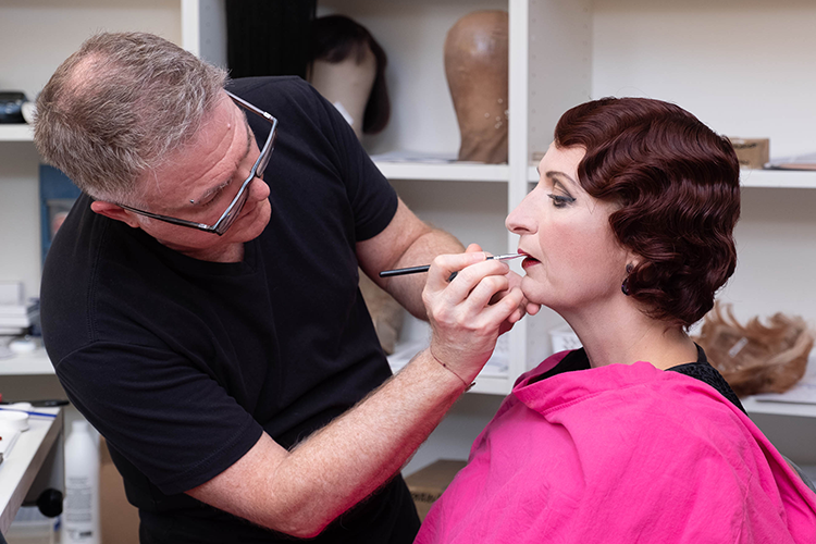 A woman sits in a chair, having her makeup done by a man.